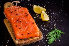 Fresh salmon fillet with lemon and dill. On dark background Royalty Free Stock Photo