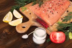 Fresh salmon fillet with aromatic herbs, spices and vegetables. Fresh salmon fillet with lemon, salt, tomato, herbs on wooden background. Close up. Top view Royalty Free Stock Image
