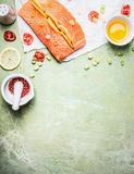 Fresh salmon fillet with lemon slices and cooking ingredients on light background, top view Royalty Free Stock Photo