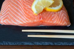 Fresh salmon fillet with lemon and wooden chopsticks on dark sto. Fresh delicious salmon fillet and wooden chopsticks dark stone background. Top view. Closeup Stock Photography
