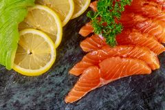 Fresh salmon fillet, lemons, avocados, parsley and spices on marble cutting board. On ready to eat fish meal gourmet healthy cuisine diet red tasty seafood stock images