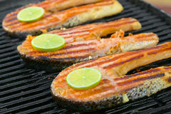 Fresh salmon fillet with lime cooked on a grill royalty free stock images
