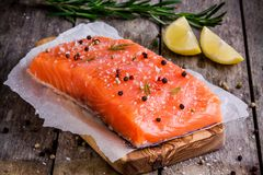 Fresh salmon fillet with pepper, lemon and rosemary. On a wooden rustic background Royalty Free Stock Image