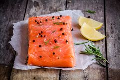 Fresh salmon fillet with pepper, lemon and rosemary. On a wooden rustic background Royalty Free Stock Photos