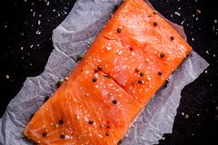 Fresh salmon fillet with pepper and sea salt. On dark background Stock Images