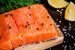 Fresh salmon fillet with pepper, sea salt and lemon. Fresh salmon fillet with peppe, sea salt and lemon on dark background Royalty Free Stock Images