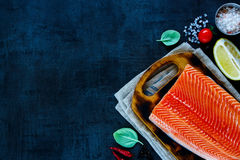 Fresh salmon fillet. Portion of fresh uncooked salmon fillet with lemon, herbs and spices on little wooden cutting board over dark rustic background - healthy Royalty Free Stock Photos