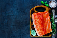 Fresh salmon fillet. Raw uncooked salmon fillet with aromatic herbs and spices on little wooden cutting board over dark rustic background - healthy food, diet or Royalty Free Stock Photos