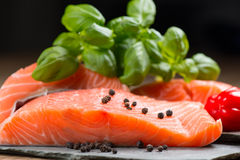 Fresh salmon fillet on rock. Fresh salmon fillet with basil and pepper on flat rocks Royalty Free Stock Images