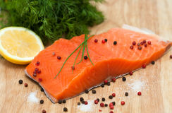 Fresh salmon fillet with sea salt, pink, black pepper and lemon Stock Photo
