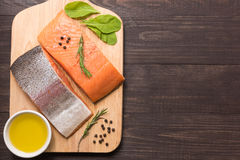 Fresh salmon fillet with spice on wooden background Stock Images