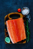 Fresh salmon fillet. Fresh uncooked salmon fillet with aromatic herbs and spices on little wooden cutting board over dark rustic background - healthy food, diet Stock Images