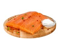 Fresh salmon fillet on wooden cutting board on white background,. Side view Stock Photo