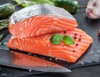 Fresh salmon fillets on black cutting board with herbs and spice stock image