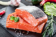 Fresh salmon fillets on black cutting board with herbs and spice. S Royalty Free Stock Photography