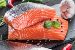 Fresh salmon fillets on black cutting board with herbs and spice. S Stock Photo