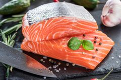 Fresh salmon fillets on black cutting board with herbs and spice. S Royalty Free Stock Images