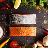 Fresh salmon fillets in a frame of ingredients. Fresh uncooked salmon fillets placed one up, one down, in a frame of ingredients for cooking the meal including stock images