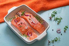 Fresh salmon fillets with onions, pepper and herbs Stock Photography