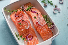 Fresh salmon fillets with onions, pepper and herbs Royalty Free Stock Image