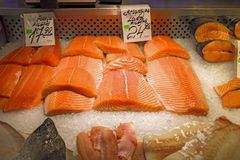 Fresh salmon fillets for sale on ice in supermarket store in fridge display. Red fish stock photography