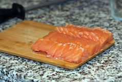 Fresh salmon fish with knife on wooden cooking desk. Cutted Fresh salmon fish with knife on wooden cooking desk royalty free stock photos