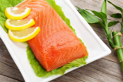 Fresh salmon fish with lemon and salad leaves Stock Image