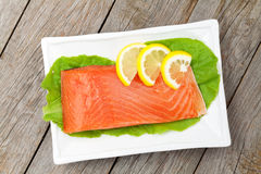 Fresh salmon fish with lemon and salad leaves Royalty Free Stock Photos