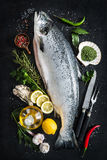 Fresh salmon. Fish with seasoning on black stone background Royalty Free Stock Photos