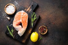 Fresh salmon fish steak. On cutting board with spices and herbs on rusty stone table. Top view copy space Royalty Free Stock Photo