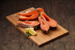 Fresh salmon fish steaks on the wooden cutting board. With lemon and greens Royalty Free Stock Images