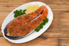 Fresh salmon with herbs and lemon on white dish Stock Photos