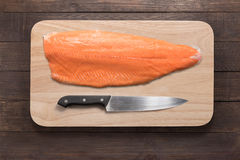 Fresh salmon and knife on cutting board on the wooden table. Top Stock Photography