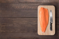 Fresh salmon and knife on cutting board on the wooden table. Top Royalty Free Stock Image