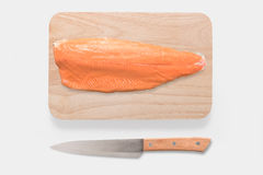 Fresh salmon and knife on cutting board on the wooden table. Top. View Royalty Free Stock Photo