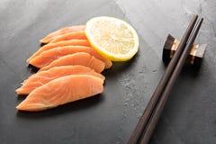 Fresh salmon with lemon on black background Stock Images