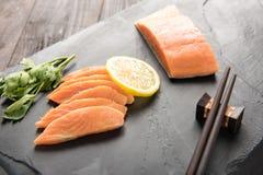 Fresh salmon with lemon on black background.  Royalty Free Stock Photography