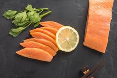 Fresh salmon with lemon on black background.  Stock Images