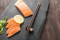 Fresh salmon with lemon on black background.  Royalty Free Stock Image