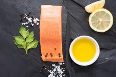 Fresh salmon with lemon on black background.  Stock Image