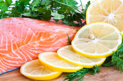 Fresh salmon with lemon and herbs. Fresh fish with lemon, dill and parsley Royalty Free Stock Image