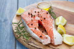 Fresh salmon with lemon, oil and rosemary on wooden board Royalty Free Stock Photography