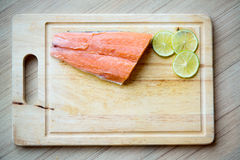 Fresh salmon, lemon slice on wood chopping board.  image for background. Wallpaper and copy space. fresh ingredient for clean food concept Royalty Free Stock Photo