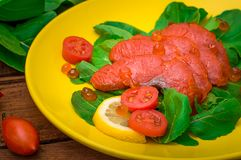 Fresh salmon with lemons and spinach on a wooden rustic background. Top view. Selective focus. Fresh salmon with lemons and spinach on a wooden rustic background Royalty Free Stock Images