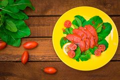 Fresh salmon with lemons and spinach on a wooden rustic background. Top view. Selective focus. Fresh salmon with lemons and spinach on a wooden rustic background Royalty Free Stock Photography