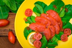 Fresh salmon with lemons and spinach on a wooden rustic background. Top view. Selective focus. Fresh salmon with lemons and spinach on a wooden rustic background Stock Photo