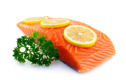 Fresh salmon with parsley and lemon. Raw salmon fillet with parsley and lemon on white background Stock Photography