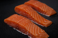 Fresh salmon pieces on dark black background stock photos