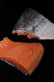 Fresh salmon pieces on dark black background royalty free stock photo