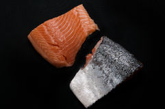 Fresh salmon pieces on dark black background stock images